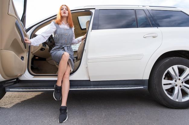 Motorista muito elegante jovem em vestido casual e tênis sentado no carro novo caro.