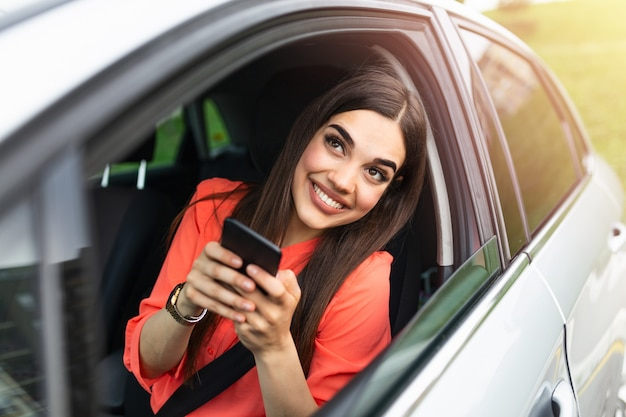 Motorista mulher usando um telefone inteligente no carro.