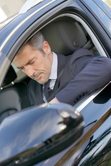 Motorista particular dentro do carro à espera de cliente