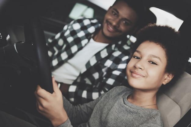 Motorista pequena orgulhosa no carro pai pai filho pequeno.