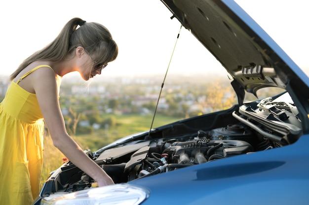 Motorista perplexa em pé perto de seu carro com o capô levantado, olhando para o motor quebrado.