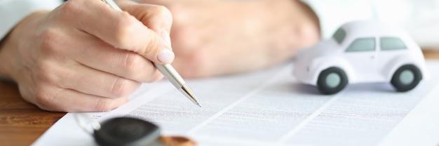 Motorista preenchendo documentos com caneta perto do carro de brinquedo, close-up