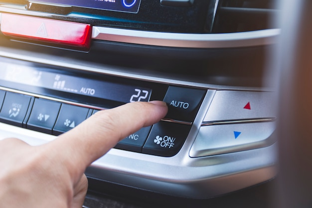 Motorista, pressionando o botão de refrigeração automática do ar condicionado do carro