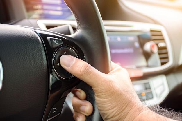 Motorista, pressionando o botão de volume no volante de um auto-rádio
