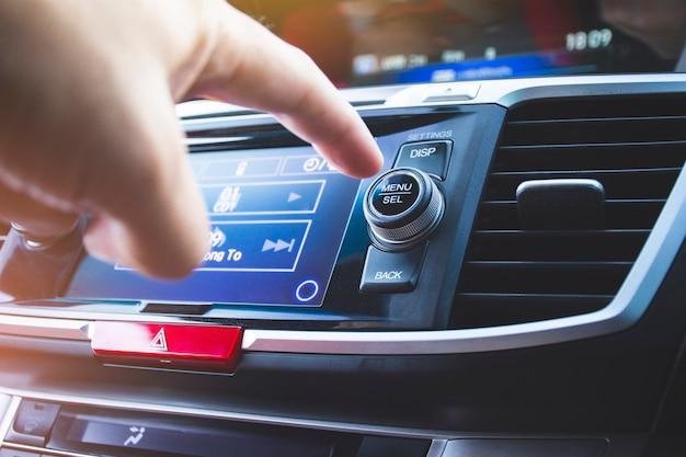 Motorista pressionando o botão menu / selecionar rádio do carro