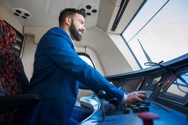 Motorista profissional sentado na cabine e operando em trem de alta velocidade