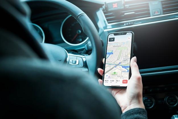 Motorista que usa o telefone celular moderno com navegação dos gps do mapa no carro.