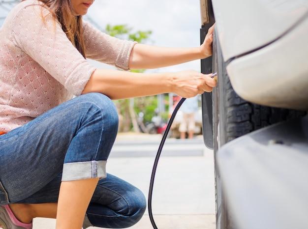 Motorista que verifica a pressão de ar e o ar de enchimento nos pneus.