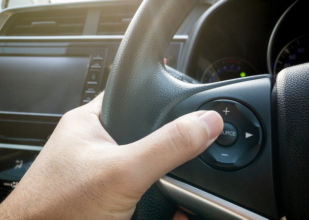Motorista segurando no volante do carro moderno com botões multi-controladores