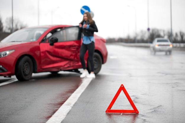 Motorista sentado na estrada após um acidente de trânsito. o foco está no sinal do triângulo vermelho