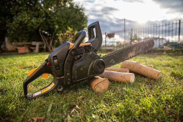 Motosserra apoiada em pedaços de madeira recém-cortados