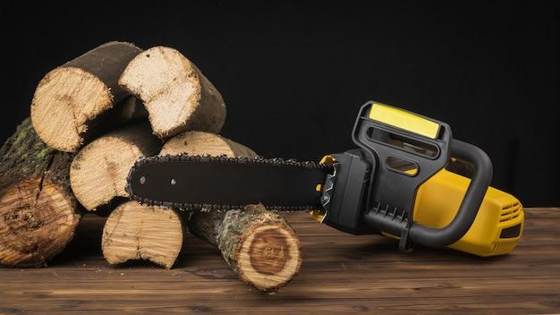 Motosserra com peças de madeira serrada em um fundo de madeira. ferramenta elétrica para processamento de madeira.