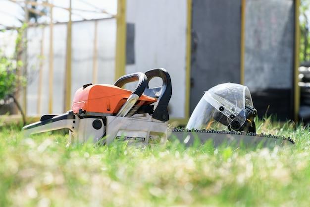 Motosserra e protetor facial, capacete na grama verde em um dia ensolarado. o conceito é cortar árvores