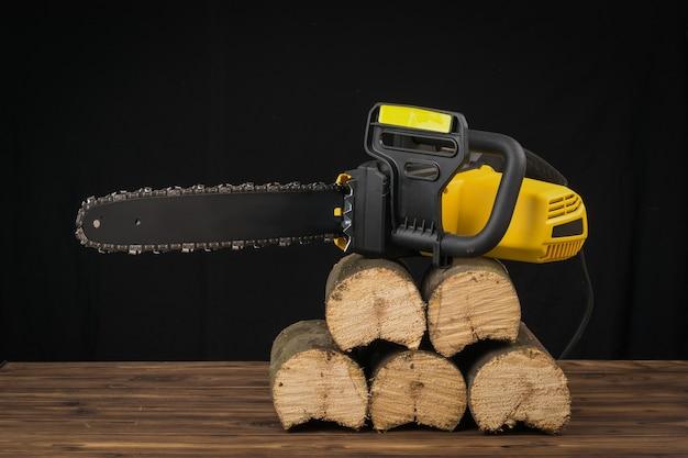 Motosserra elétrica em toras de madeira serradas. ferramenta elétrica para processamento de madeira.