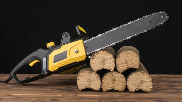 Motosserra elétrica em toras serradas em um fundo preto. ferramenta elétrica para processamento de madeira.
