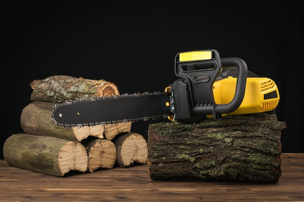 Motosserra elétrica em um tronco de madeira no fundo das árvores serradas. ferramenta elétrica para processamento de madeira.