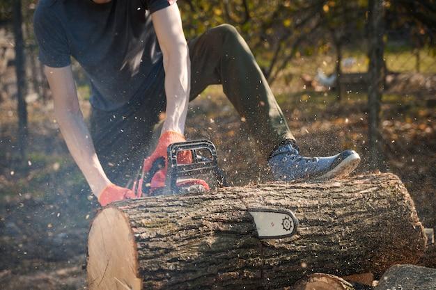 Motosserra que fica em uma pilha de lenha no quintal de grama verde e floresta. cortar madeira com um testador de motor