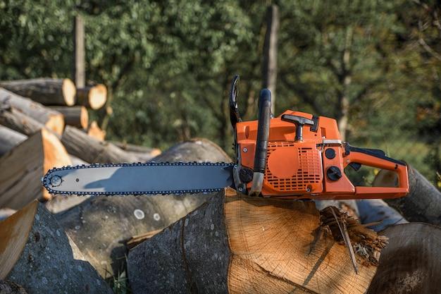 Motosserra que fica sobre um monte de lenha no quintal em um fundo de lenha e árvores cortadas por uma motosserra.