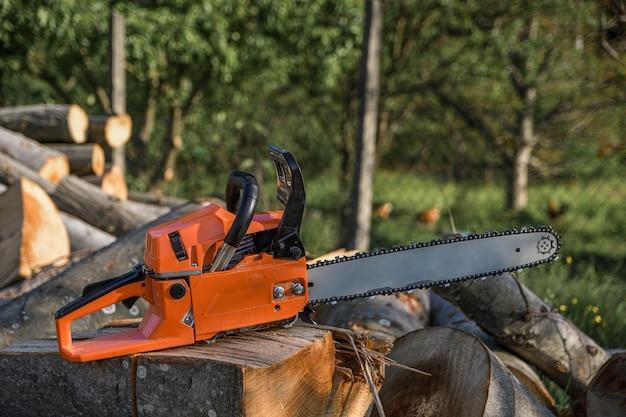 Motosserra que fica sobre um monte de lenha no quintal em um monte de lenha e árvores cortadas por uma motosserra.