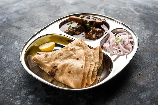 Motton thali ou gosht, prato de cordeiro é um almoço indiano asiático não vegetariano ou menu de jantar composto por carne, curry de ovo com chapati, arroz, salada e doce gulab jamun