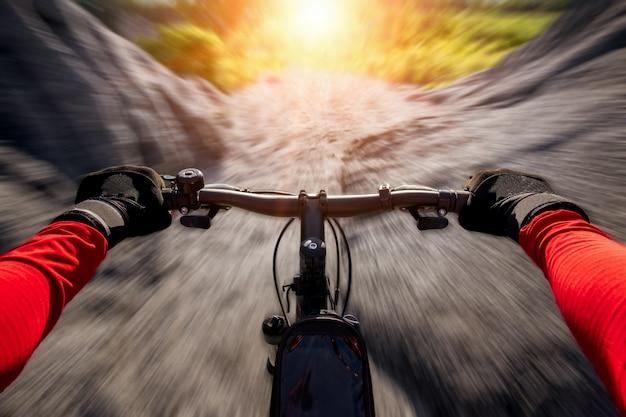 Mountain bike da equitação do ciclista na fuga rochosa no por do sol.