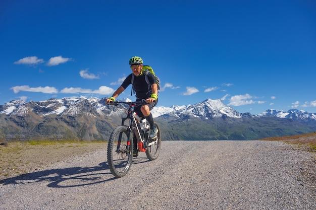Mountain bike nas altas montanhas em uma estrada de terra