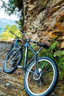 Mountain bikes pretas perto da enorme rocha marrom