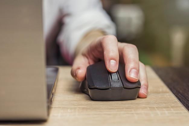 Mouse de computador em uma mão feminina, laptop em uma mesa de madeira. cena do ambiente de trabalho