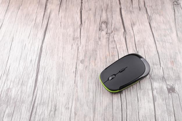 Mouse de computador sem fio em fundo de madeira