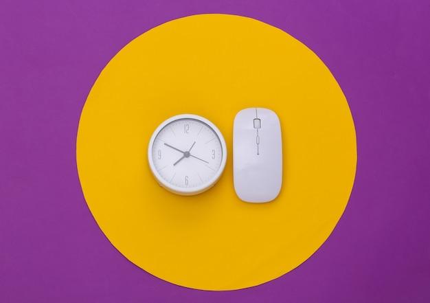 Mouse de pc branco e relógio em fundo roxo com círculo amarelo. foto de estúdio conceitual. minimalismo. vista do topo