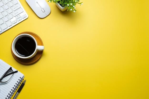 Mouse do teclado do caderno da caneca de café colocado no fundo amarelo. copie o espaço.