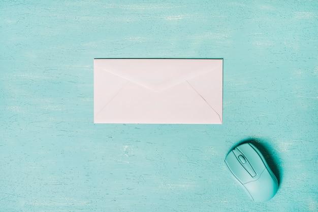 Mouse e envelope branco em fundo texturizado de madeira turquesa