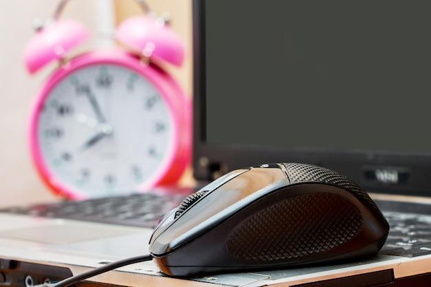 Mouse perto de um laptop e um relógio