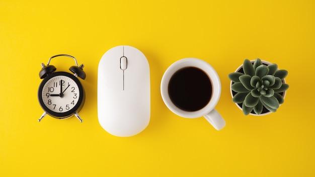 Mouse, relógio e xícara de café em fundo amarelo