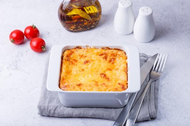 Moussaka com carne, berinjela, tomate, batata, molho bechamel e queijo em um prato branco. prato tradicional grego. fechar-se.