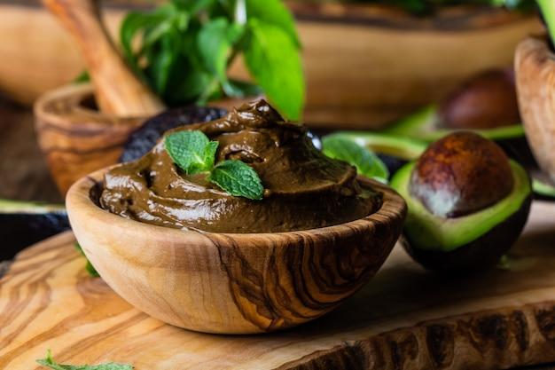 Mousse de chocolate com abacate na tigela de madeira verde-oliva
