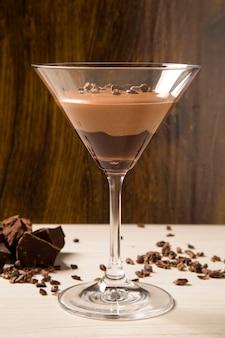 Mousse de chocolate em um copo sobre uma superfície de madeira