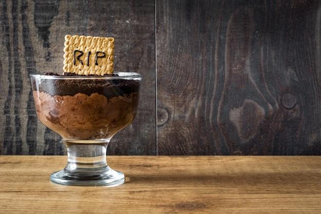Mousse de chocolate engraçado halloween com biscoito de tumba e aranhas no espaço da cópia de mesa de madeira