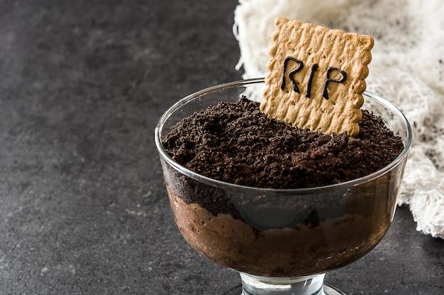 Mousse de chocolate engraçado halloween com biscoito de túmulo no espaço da cópia de pedra preta
