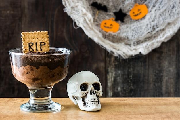 Mousse de chocolate engraçado halloween com biscoito túmulo e aranhas na mesa de madeira cópia espaço