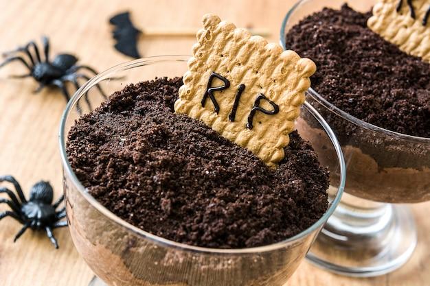 Mousse de chocolate engraçado halloween com biscoito túmulo e aranhas na mesa de madeira fechar