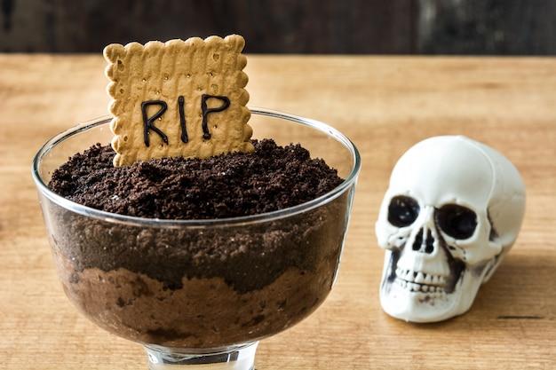 Mousse de chocolate engraçado halloween com biscoito túmulo e aranhas na mesa de madeira
