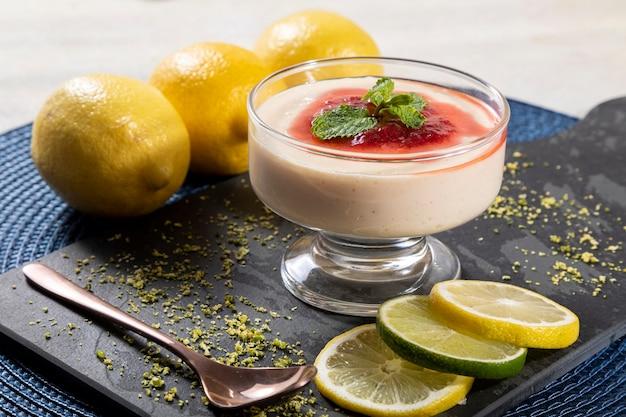 Mousse de limão em tigela de cristal com cobertura de geleia de morango e hortelã.