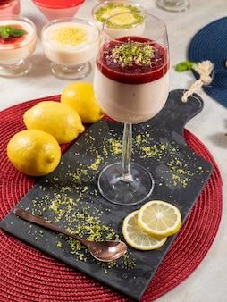 Mousse de limão em tigela de cristal com cobertura de geleia de morango e raspas de limão.