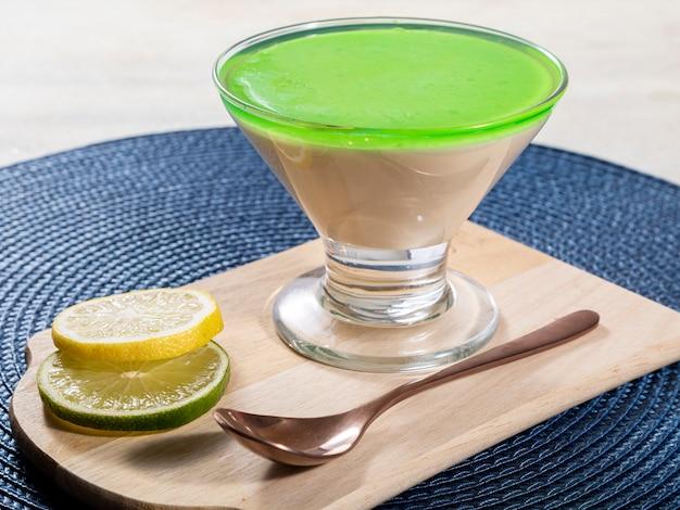 Mousse de limão em uma tigela de vidro com gelatina de limão por cima.