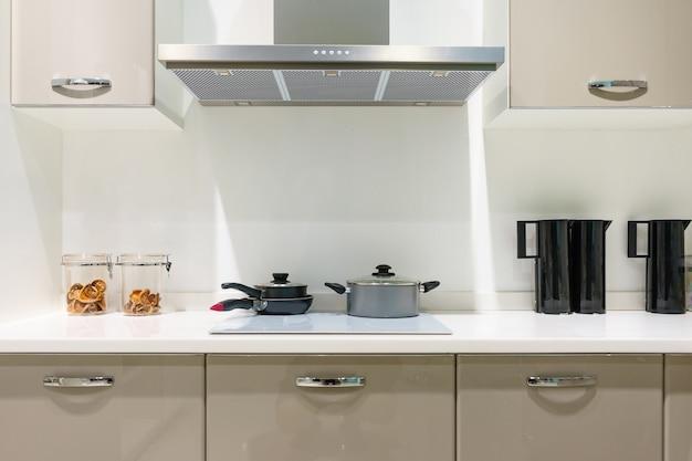 Móveis de cozinha com utensílios contemporâneos como capô, fogão de indução preto e forno