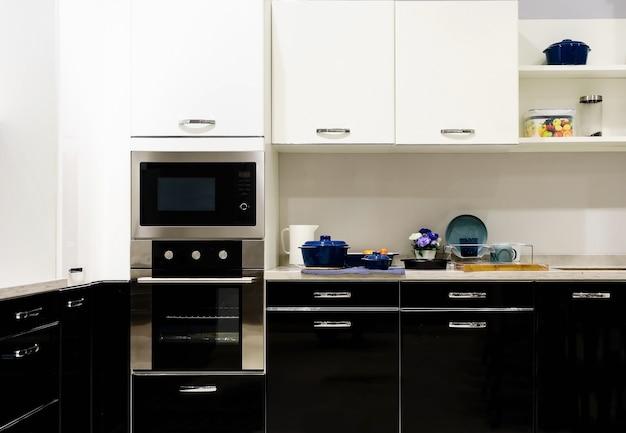 Móveis de cozinha com utensílios contemporâneos, como capô, fogão de indução preto e forno