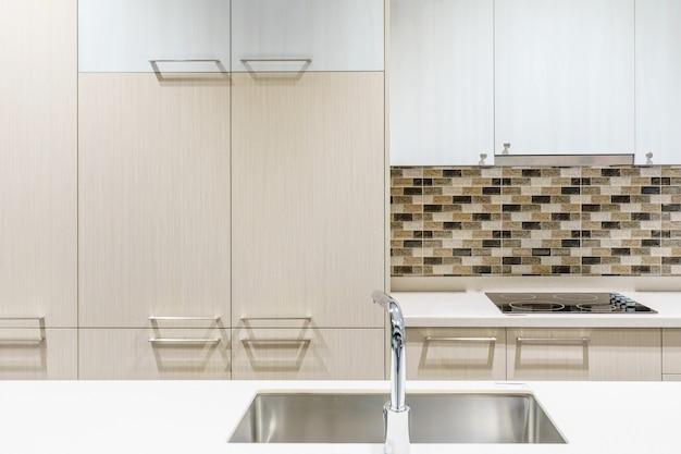Móveis de cozinha com utensílios de cozinha contemporânea como capô, torneira e pia em casa.
