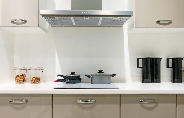 Móveis de cozinha moderna com utensílios de cozinha contemporânea, como capuz, fogão de indução preto e