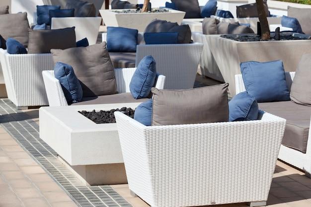 Móveis de exterior, poltronas de vime e mesa no terraço